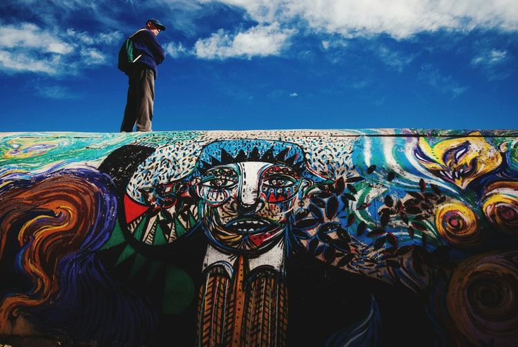 Low Angle View Of Man Standing On Graffiti Wall Against Sky