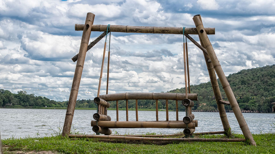 View of swing in playground against cloudy sky