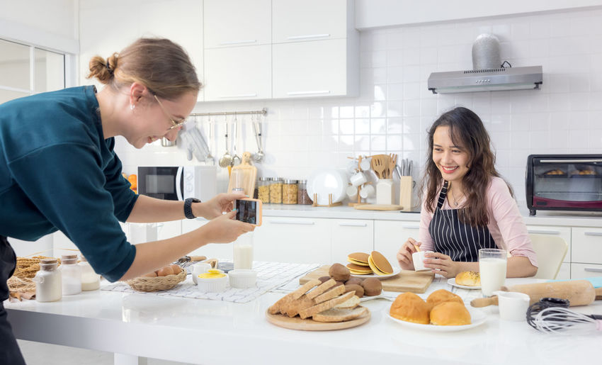Young woman holding food on table in kitchen