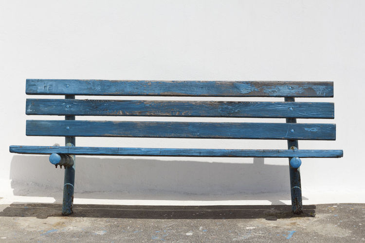 Empty bench on table against clear blue sky