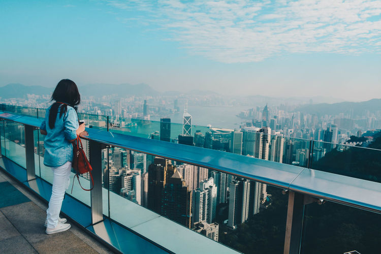 Woman standing on terrace against cityscape