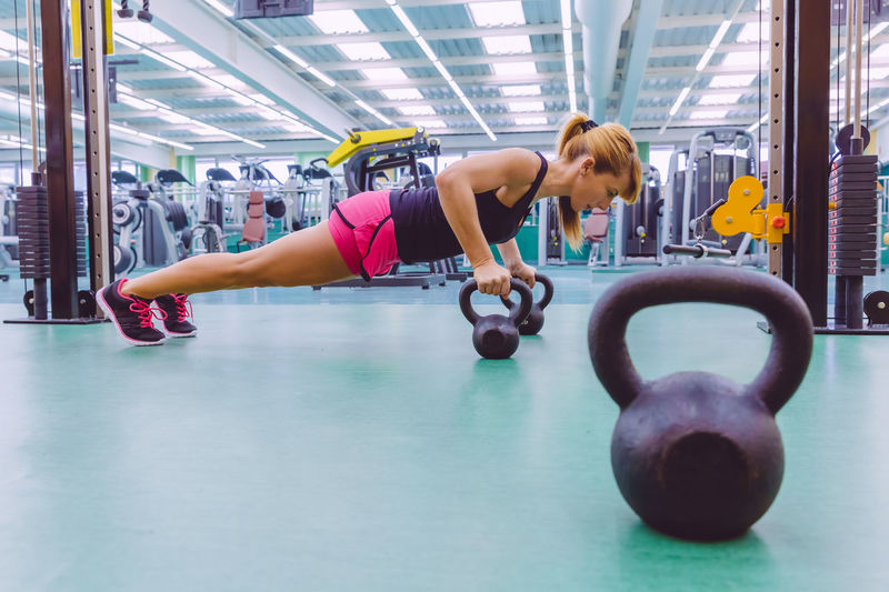 Full Length Of Woman Doing Push-Ups With Kettlebell At Gym