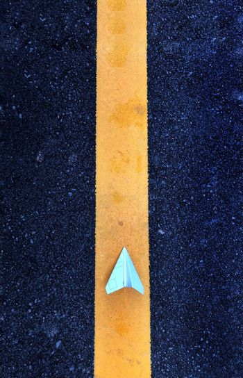 Directly above shot of paper airplane on road