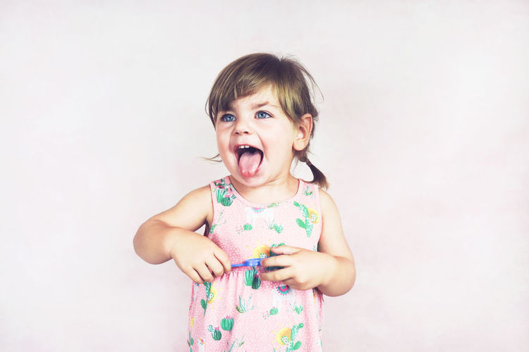 Childhood Child One Person Studio Shot Happiness Girls Emotion Innocence Standing Portrait Indoors  Smiling Front View White Background Looking At Camera Cute Women Casual Clothing Mouth Open Hairstyle Bangs Funny Sticking Out Tongue Crazy Lovely