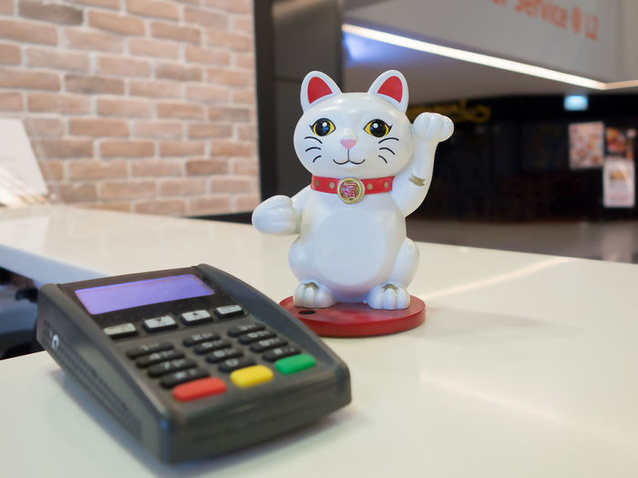 A lucky cat waving hand beside a POS terminal on white cashier counter in a shopping mall. Business Lucky Machine Shopping Statue Car Cashier  Cat Counter Ecommerce Fortune Indoors  Money Pos Sculpture Shop Shopping Mall Store Table Terminal