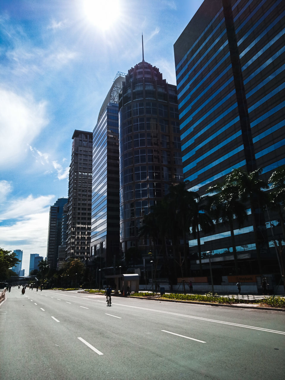 city, building exterior, built structure, architecture, road, sky, building, office building exterior, street, transportation, office, tall - high, nature, skyscraper, modern, symbol, tower, cloud - sky, sunlight, day, no people, outdoors, financial district