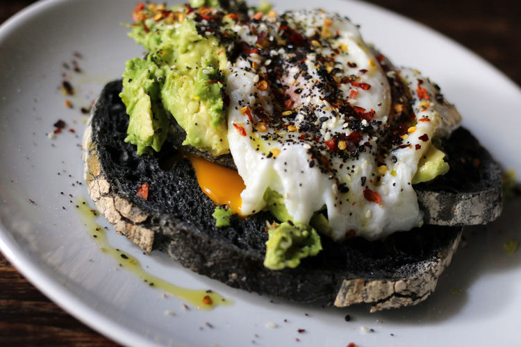 Avocado toast served with poached egg Avocado Black Bread Bread Breakfast Breakfast Brunch Close-up Day Egg Egg Yolk Food Food And Drink Freshness Indoors  No People Plate Poached Poached Egg Poached Eggs  Ready-to-eat Serving Size Spices Toasted Toasted Bread