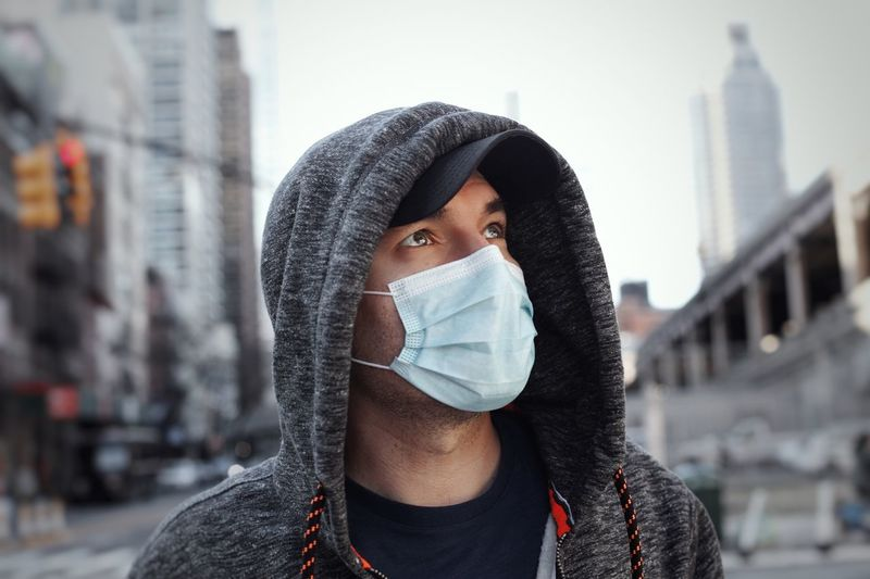 Man wearing mask and standing in city