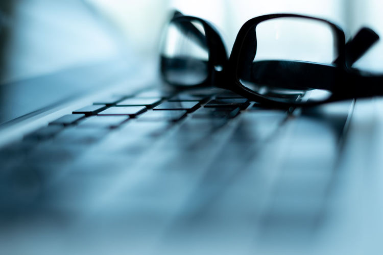 black glasses put on laptop keyboard. selective and soft focus. subject is blurred Glasses Keyboard Laptop Notebook Eye Eyeglasses  Online  Work Job Office Computer Desk Business Technology PC Internet Communication Education Electronic Tech Black Typing Closeup Modern Device Information Keypad Desktop Surfing Connection Network Background Cafe Digital Blur Relax Surf Equipment Connected Close-up Wireless Concept Focus Button Communications Occupation Stationery Leadership Working