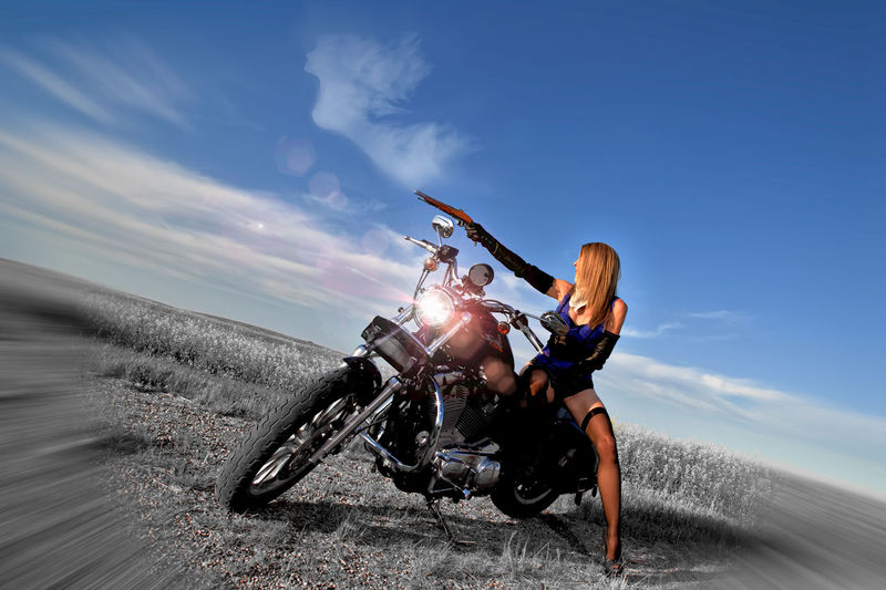 Woman with gun sitting on motorcycle against sky
