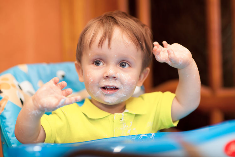 Close-up of baby boy with messy face sitting in high chair