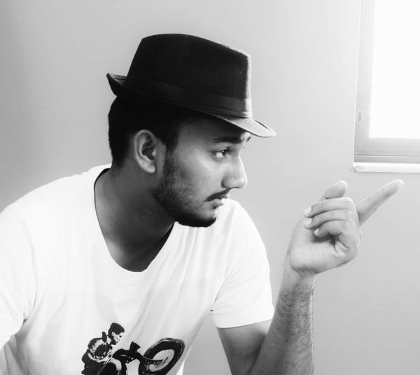 Young Man In Fedora Pointing Against Wall