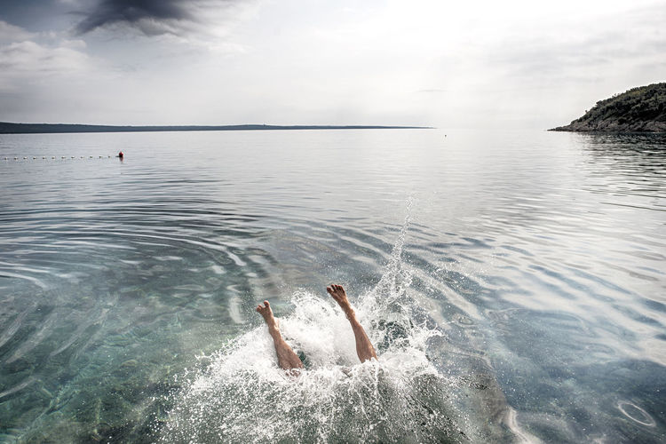 High angle view of woman drowning in sea against sky
