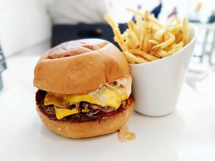 Close-up of burger with french fries on table in cafe