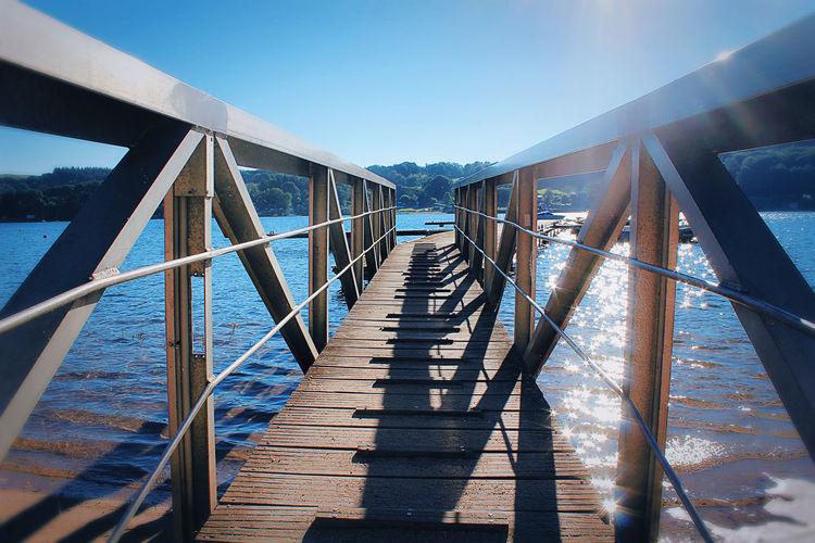 Footbridge over sea against clear blue sky