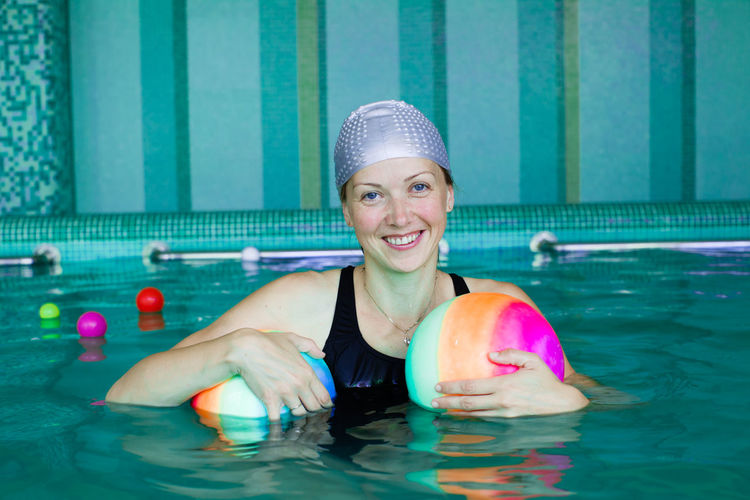 Portrait of a smiling young woman swimming in pool