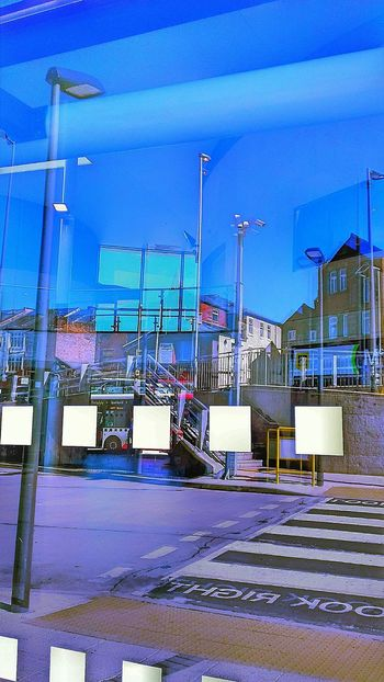 Built Structure Architecture Outdoors Sky Blue EyeEmNewHere Bright Blue Sky Double Image Bus Station Window Reflections Of Buildings Opposite Light Old And New Glass Window Town Centre Summer Street Signage Road Overlooking Buildings Tinted Glass