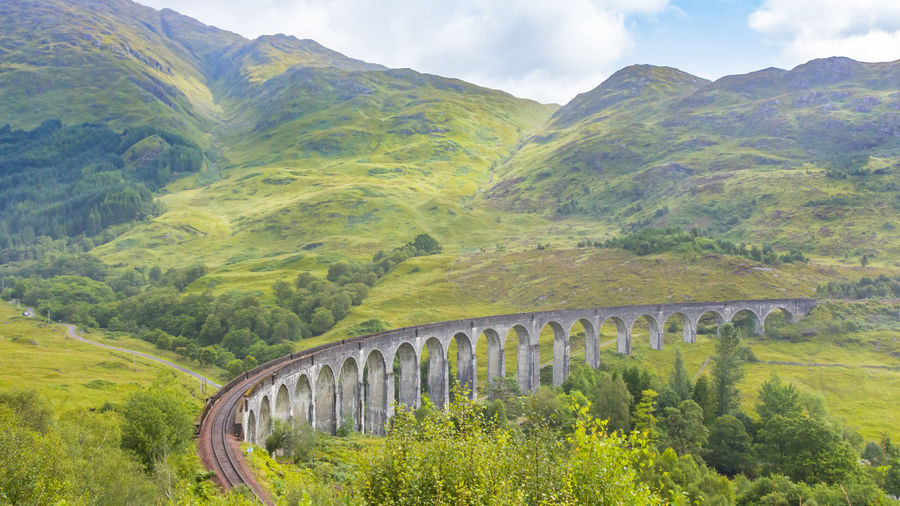 viaduct with train in Scotland View Viaduct Valley Vacations United Uk Travel Transportation Transport Train Track Tourism Summer Stone Smoke Scottish Scotland Scenic Scenery Scene Railway Railroad Potter Outdoors North Nature Mountains Locomotive Landscape Landmark KINGDOM Journey Jacobite Hill Highlands Harry Green Glenfinnan Famous Express Europe Engine Construction British Bridge Arch