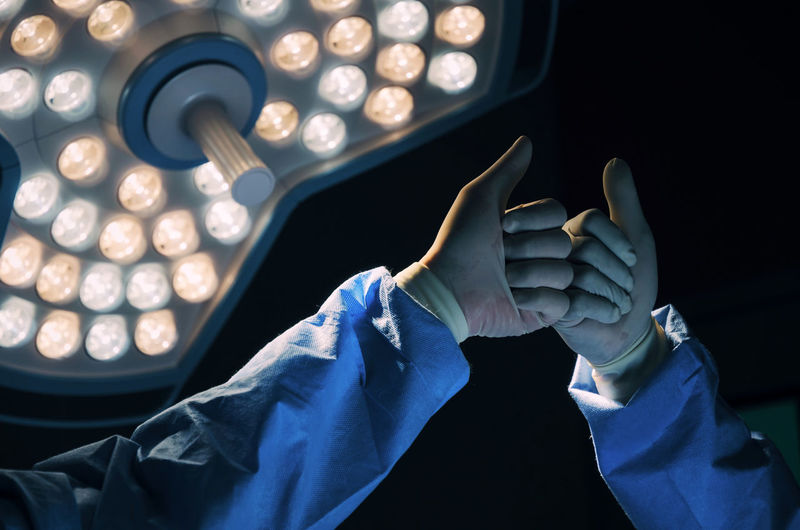 Cropped hands of surgeon giving fist bumps against illuminated lighting equipment