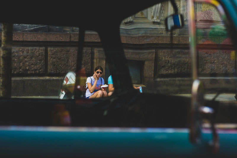 Young women eating wraps on thу sidewalk. Reflection Retro Adult Car Females Focus On Background Leisure Activity Lifestyles Old Oldsmobile Real People Sitting Togetherness Two People Vintage Cars Window Windows Women Young Adult Young Women