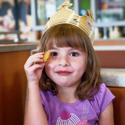 Portrait of girl holding food at restaurant