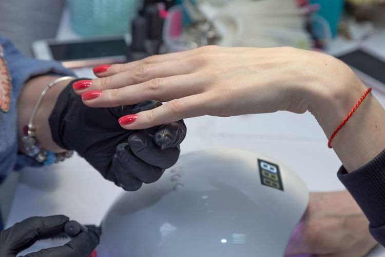 Cropped hands of manicurist applying nail polish on finger of woman