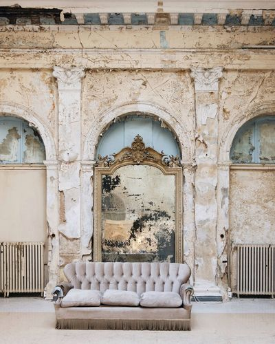Empty sofa against wall in old abandoned room