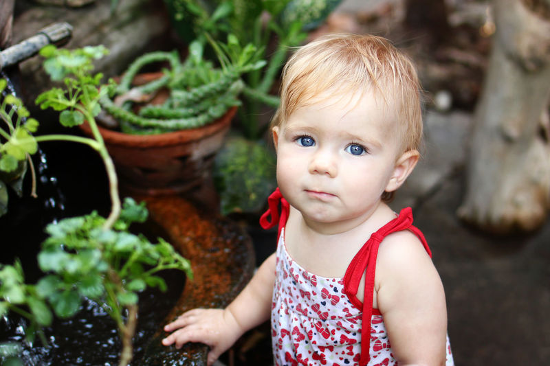Portrait of cute baby girl standing by pond