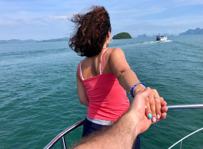 Cropped Image Of Man Holding Girlfriend Hand On Boat In Sea