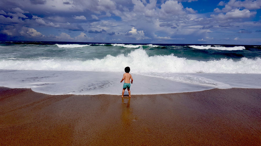 Beach Child Childhood Children Only Day Full Length Horizon Over Water Leisure Activity One Boy Only One Person Outdoors People Rear View Sand Sea Vacations Wave