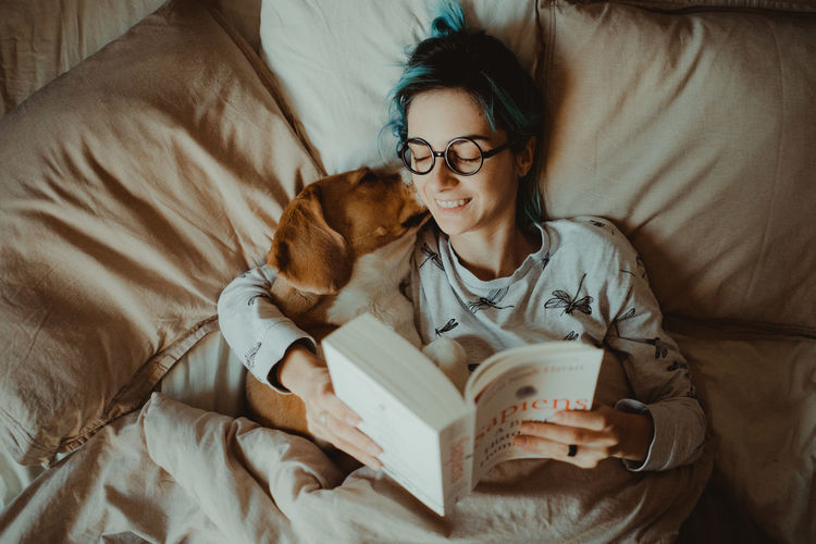 Young woman reading book while lying with dog on bed