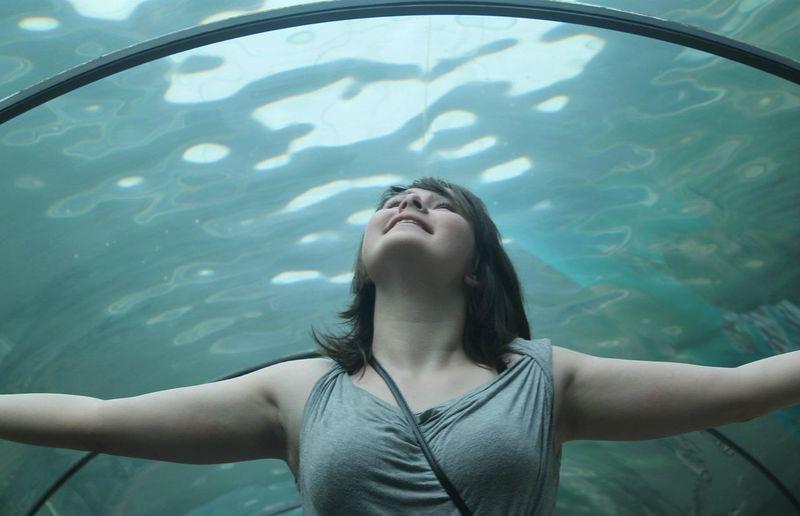 Woman looking up in aquarium