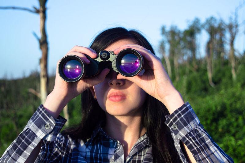 Woman looking through binoculars on sunny day