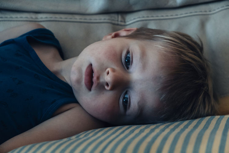 Close-up portrait of baby lying on bed at home