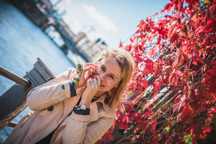 Young woman using phone while leaning on railing by creeper plant