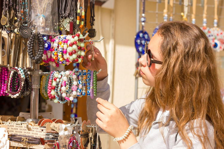 Close-up of girl wearing sunglasses buying bracelets in market