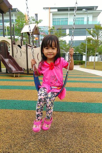 Full length of cute girl swinging at playground