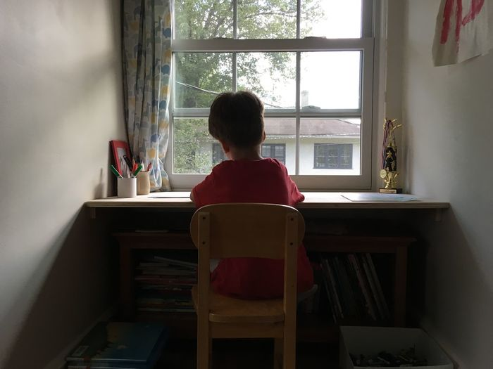 Boy Casual Clothing Day Domestic Room Drawing Home Homework Homework Time Kid Leisure Activity Lifestyles Relaxation Sitting Sitting On Table Sitting On Window Table Window Windows Writing