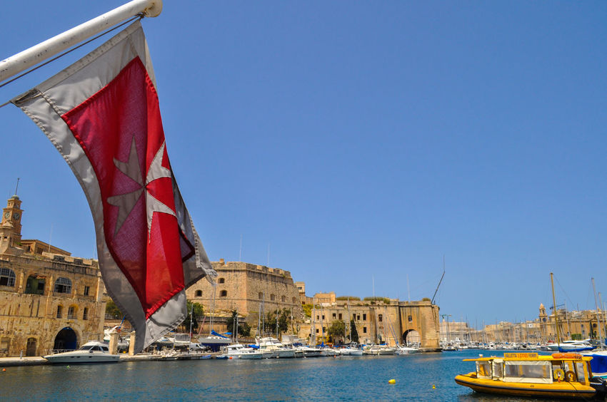In the Grand Harbour at Senglea, of The Three Cities, Malta. 3 Cities Malta Ferry Malta Senglea Travel Arch Architecture Building Exterior City Clear Sky Culture Flag Flag In The Wind Gran Harbour Grand Harbour Maltese Maltese Flag National Icon Nautical Vessel Patriotism Red Sailboat Tourism Transportation Travel Destinations