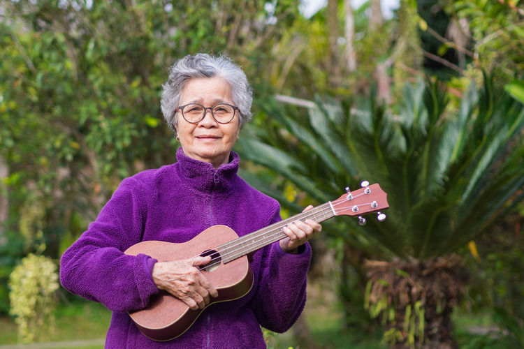 An elderly asian woman playing the ukulele while standing in a garden