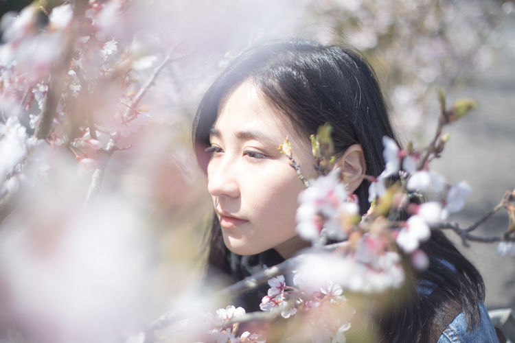 Portrait of young woman with cherry blossom