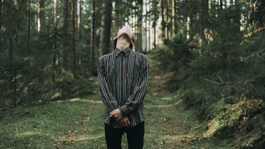 Full length of young man standing in forest with mask on