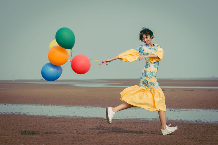 Side View Of Young Woman With Colorful Helium Balloons Running At Beach