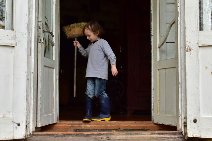 Door Childhood One Person Full Length Standing Doorway Indoors  Domestic Life Side View Child Home Interior Children Only One Boy Only Broom Sweep Time To Clean  Childhood Memories Autumn Casual Clothing Elementary Age Helper Jeans