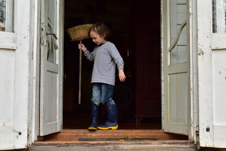 Full Length Of Boy Holding Broom On Doorway
