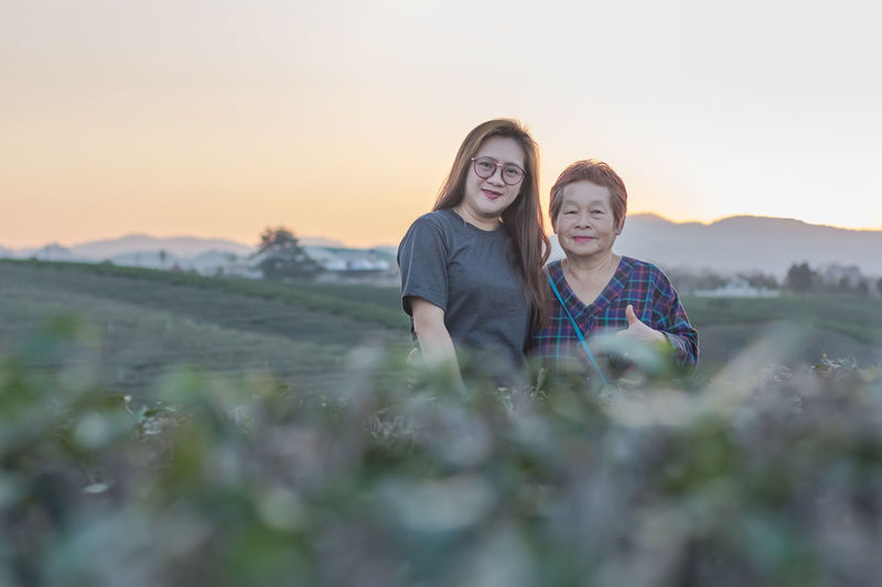 Portrait of mother and daughter standing on field against sky during sunset