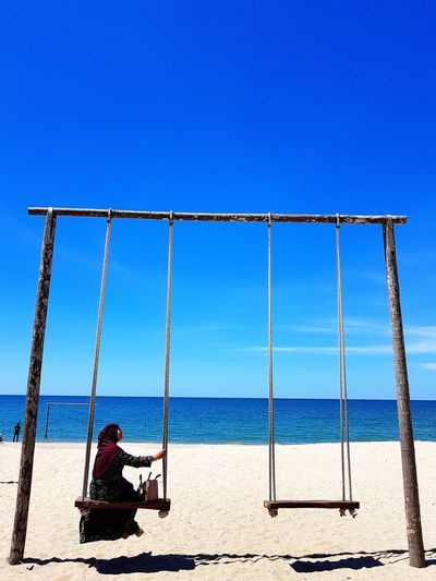 Woman in traditional clothing sitting on swing at beach against blue sky during sunny day