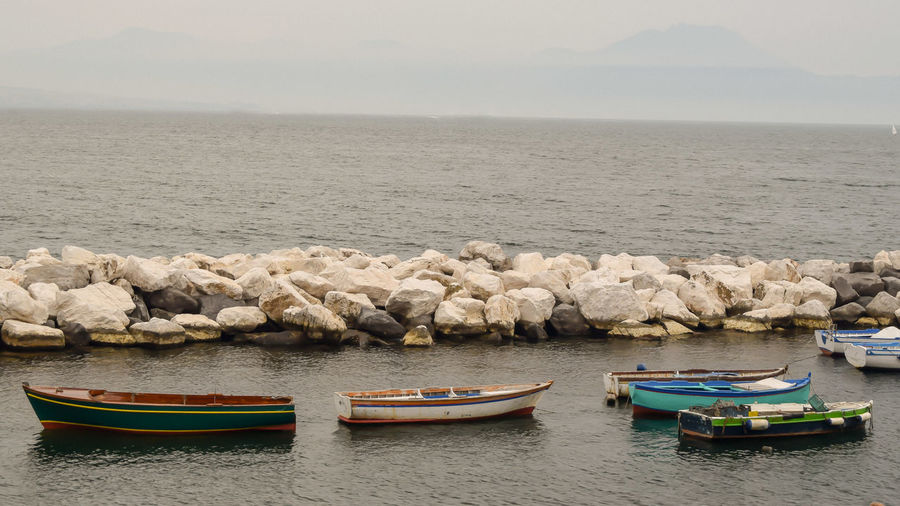 Fishing boats in sea against sky
