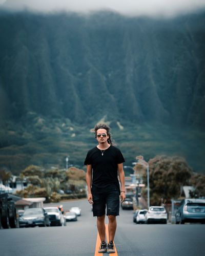 Full length portrait of man standing on road in city