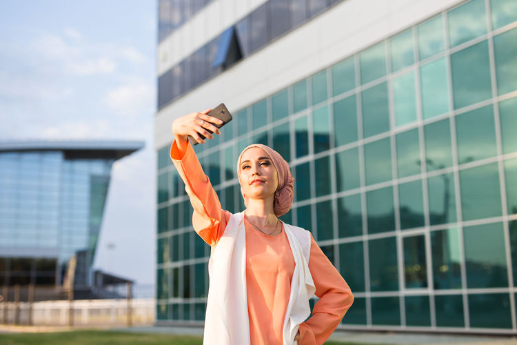 Young woman taking selfie while standing against building